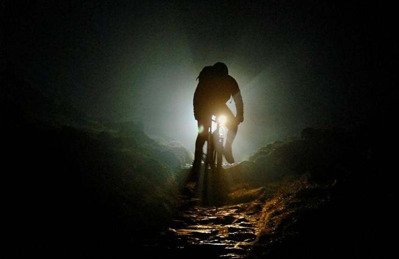 Велосипедист в темноте светит велофарой